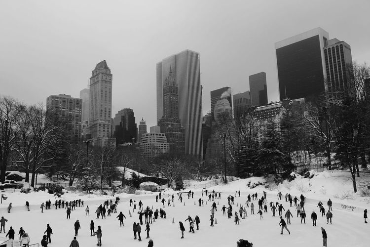 People ice-skating against towers in city
