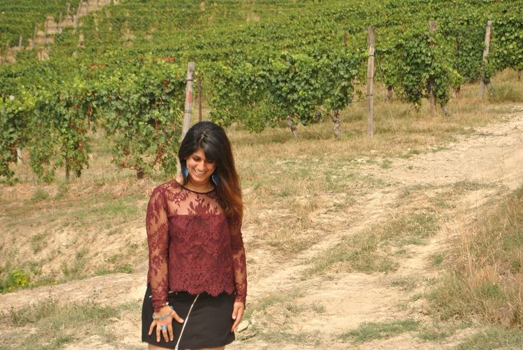Smiling young woman standing in vineyard