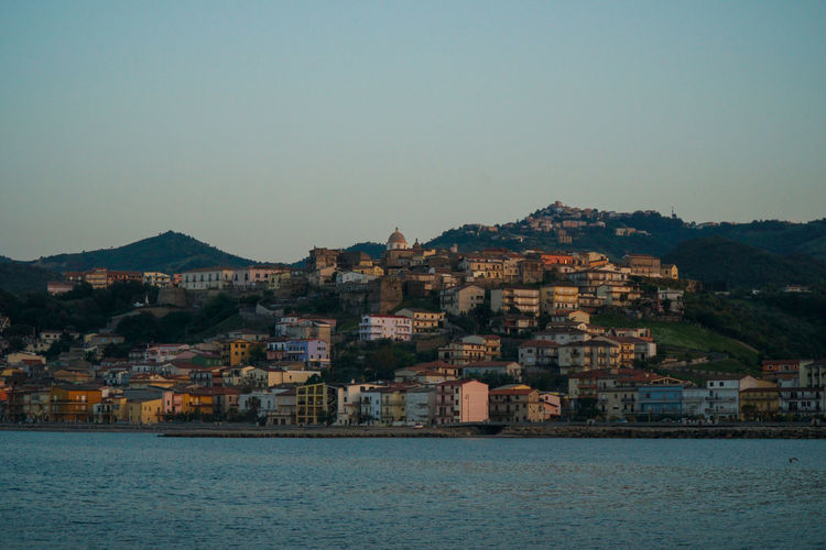 Houses on mountain by sea against clear sky during sunset