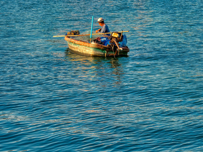 Man in boat sailing in sea