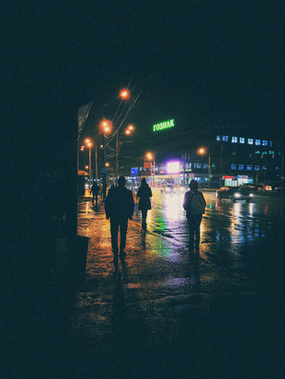 Rear view of people walking on wet road at night