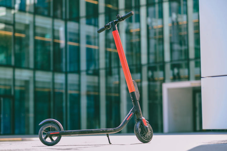 Electric push scooter parked on footpath