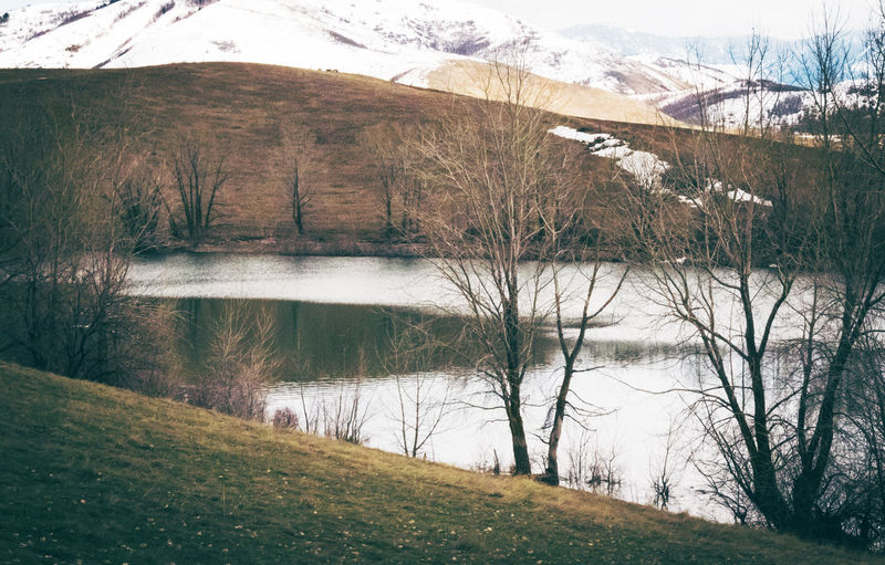 Scenic view of lake by mountains during winter