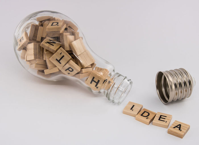 """A light bulb, with an unscrewed socket, filled with letter tiles, spitting out the word """"idea"""" on a white background. This concept photograph symbolizes the process of generating an idea. A light bulb is related to the thinking concept. It is completely stuffed with letter tiles that symbolize various ideas and concepts inside of the light bulb. Like a human brain that is filled up with concepts and ideas that are not complete. When the light bulb opens up, a concept emerges. An idea is being born after a process of thinking and shuffling letters. Visualization of brainstorm. Achievement Advertising Authentic Authentic Moments Brainstorm Bulb Business Finance And Industry Concept, Glass Creativity Design Idea, Imagination Innovation Inspiration Intellectual Property Invention Original Experiences Outdoors Pattern Simplicity Solution Success Talent Theory Thought First Eyeem Photo"""