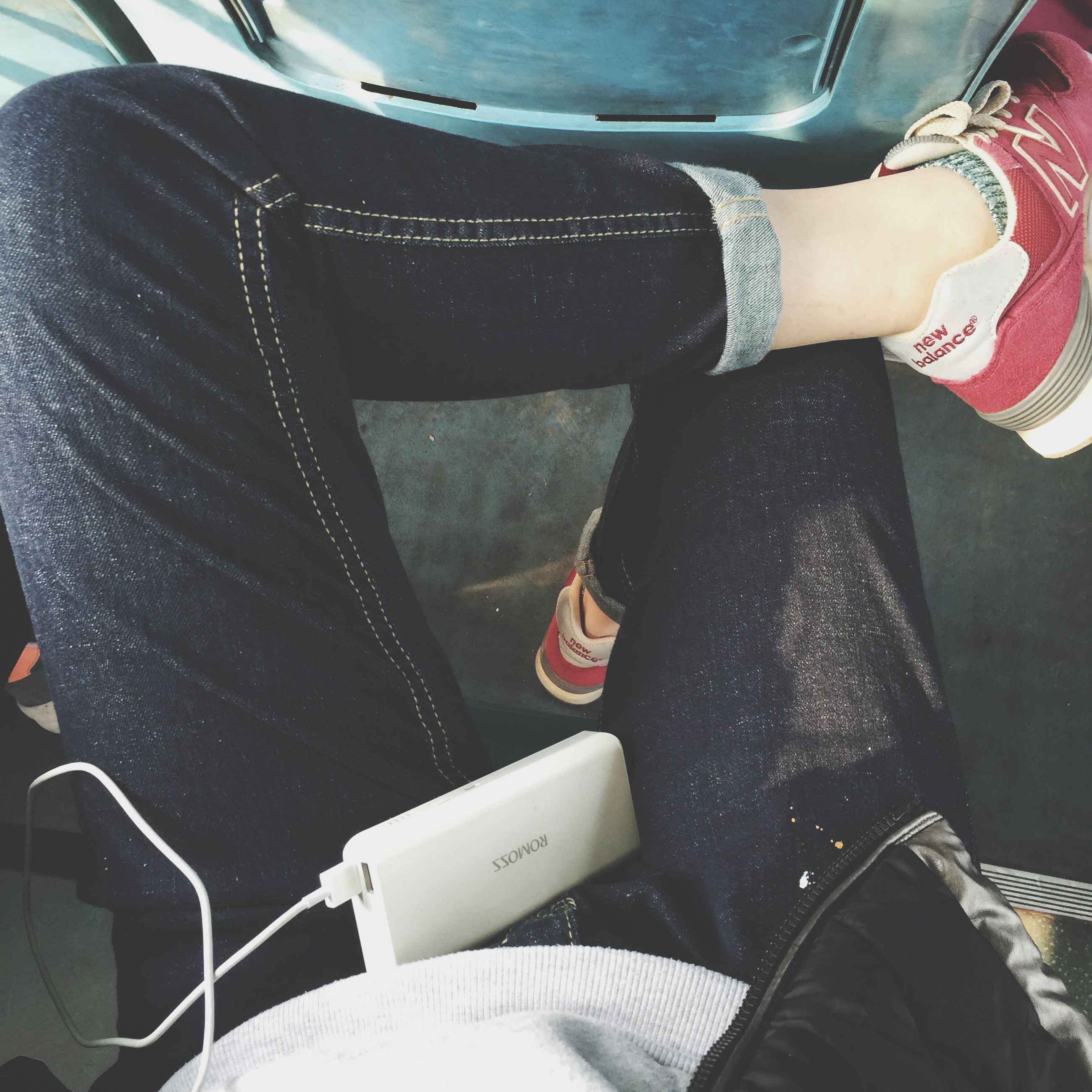 low section, person, lifestyles, part of, indoors, men, transportation, high angle view, leisure activity, midsection, sitting, holding, shoe, cropped, casual clothing, mode of transport