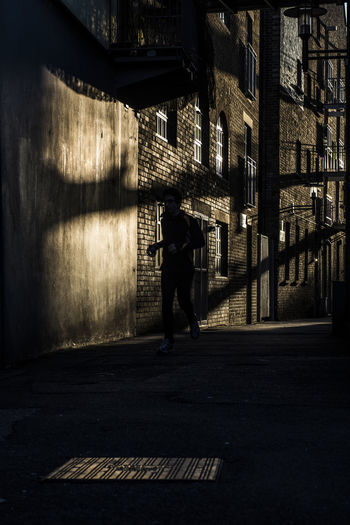 Silhouette Image Of Person Jogging On Street Against Building