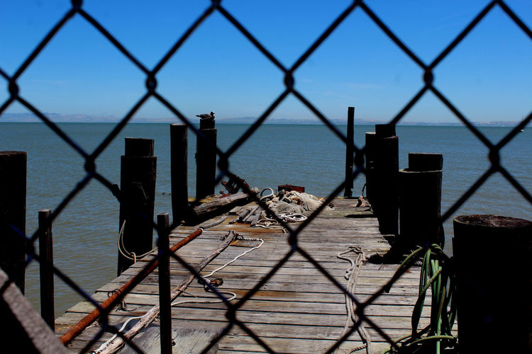 Close-up of chainlink fence against sea