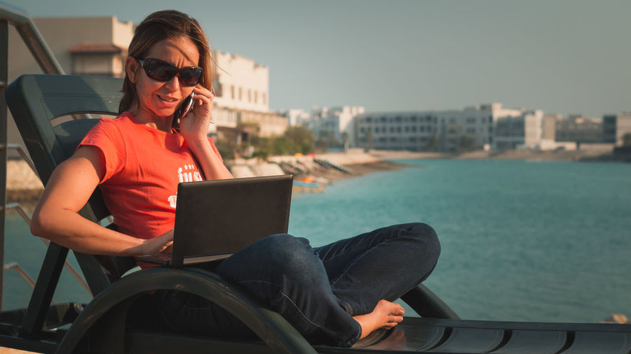 Woman Talking On Mobile Phone While Working On Laptop Against Lake