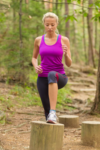 Full length of woman exercising in forest