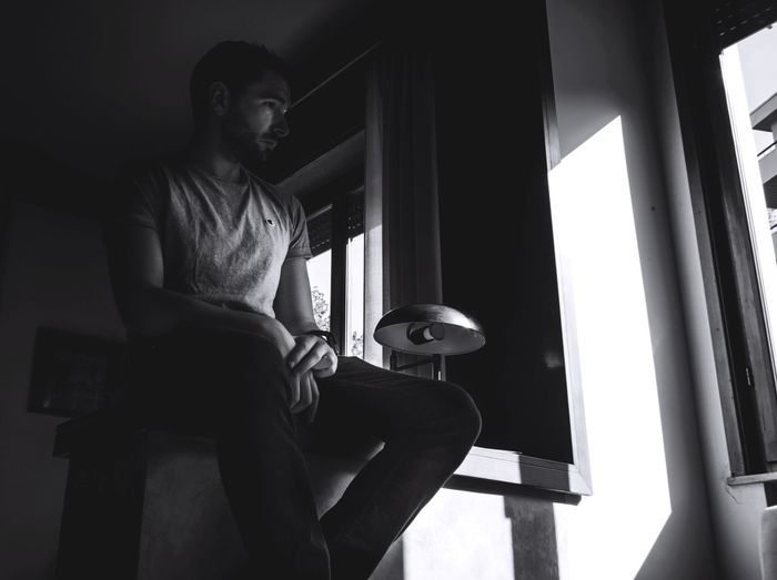 Low Angle View Of Man Looking Through Window At Home