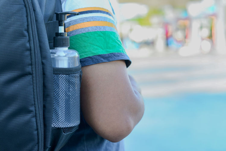 Midsection of boy with backpack and bottle