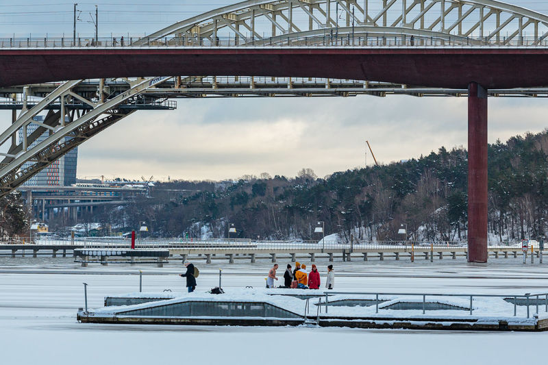 People on bridge over river against sky during winter