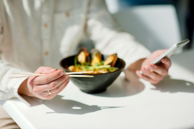 Midsection Of Person Holding Chopsticks And Phone By Food In Restaurant