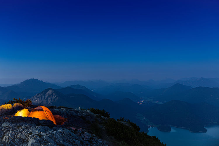 Illuminated tents on mountains against clear blue sky