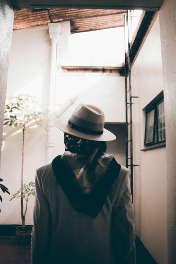 Man wearing hat standing against window