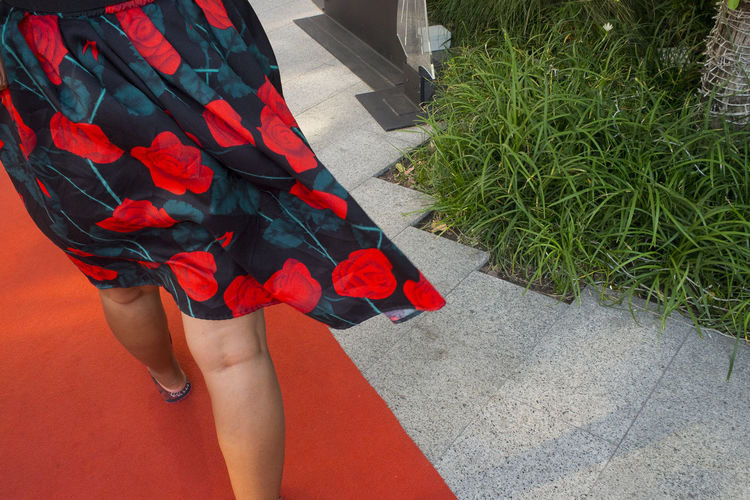 Low Section Of Woman Walking On Red Carpet