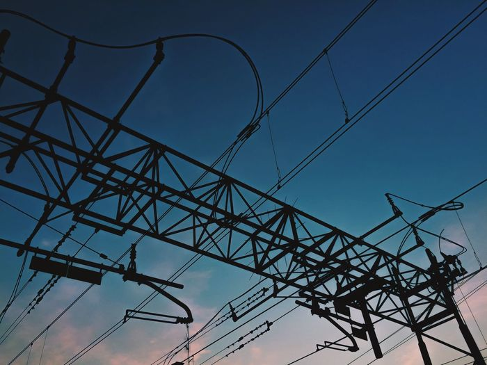 Low angle view of silhouette electric cables against blue sky during sunset