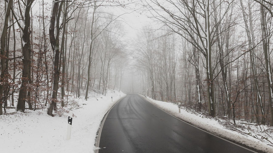 Snow covered road amidst bare trees during winter