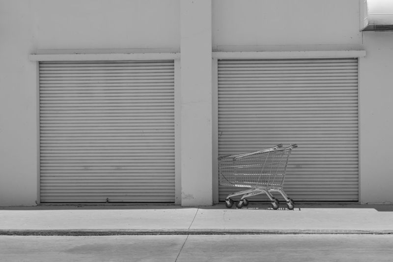 Empty Shopping Cart parked in front of large supermarket. Architecture Building Building Exterior Built Structure Closed Day Door Entrance Footpath Full Length Iron Metal No People Outdoors Shopping Shopping Cart Shutter Sidewalk Social Issues Store Trolley Wall - Building Feature