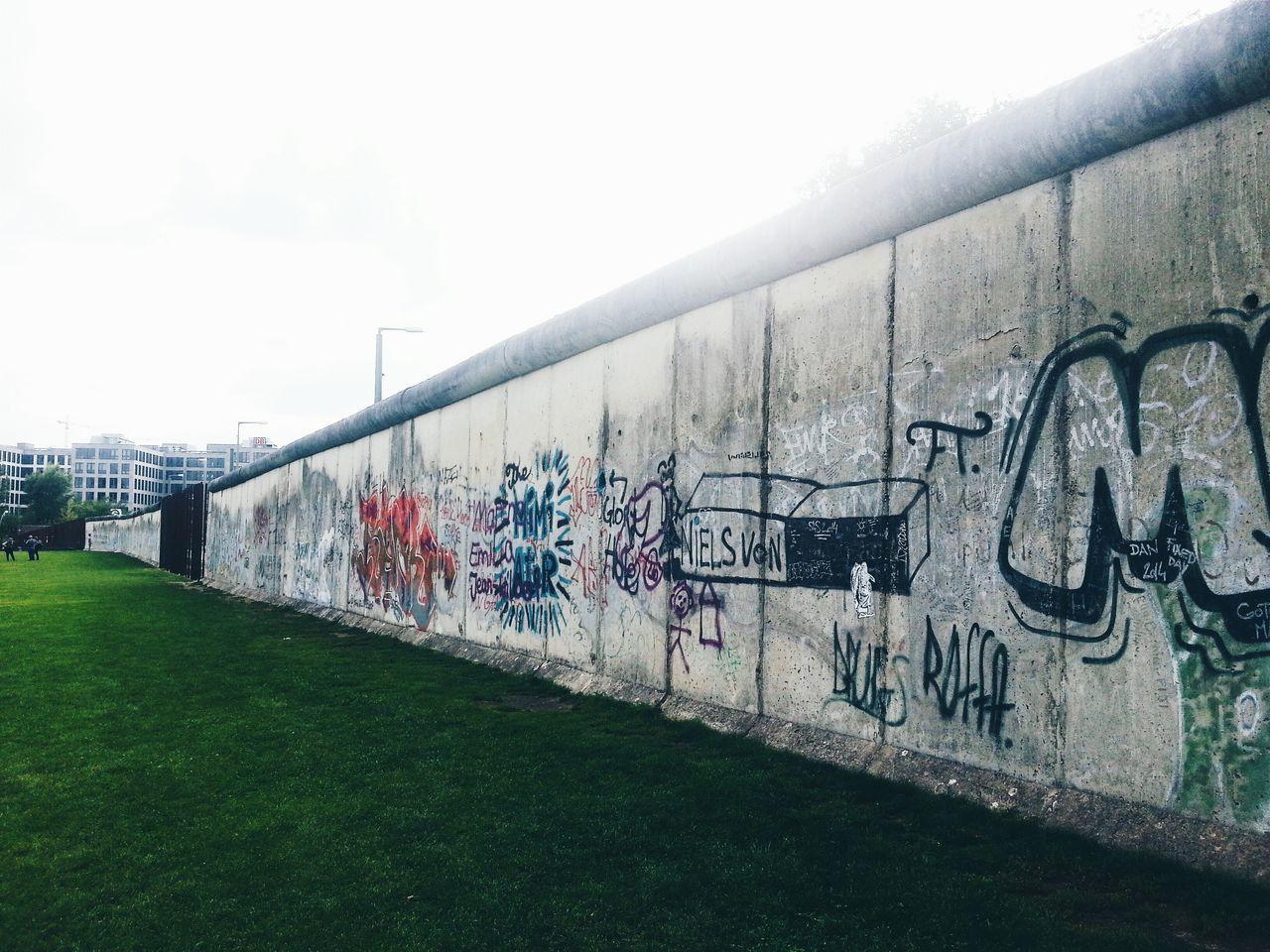 Graffiti On Berlin Wall Against Sky