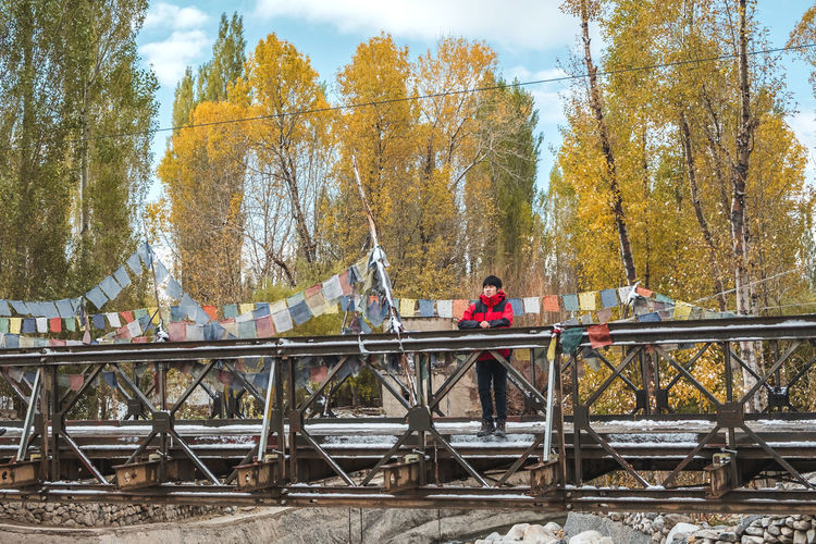 Man standing by railroad bridge against sky during autumn