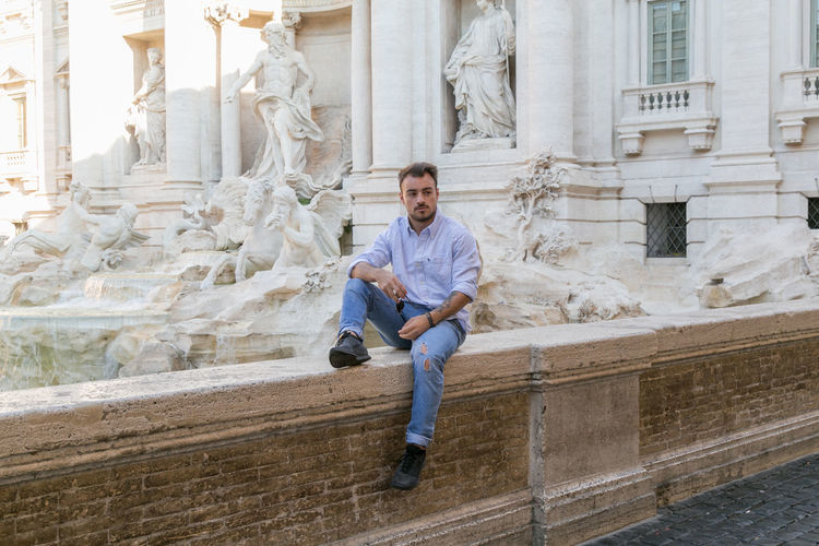 Architecture One Person Full Length Portrait Staircase Built Structure Casual Clothing Sculpture Looking At Camera Building Exterior History Statue The Past Day Front View Young Adult Men Architectural Column Sitting Outdoors Italy Italia Man Menswear Street Streetphotography Streetsyle Fashion Rome Roma The Street Photographer - 2019 EyeEm Awards