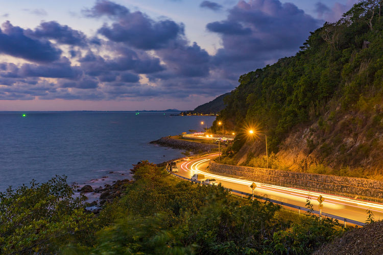 High angle view of illuminated road by sea against sky