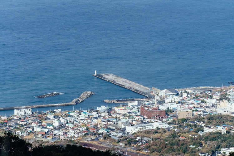 High angle view of buildings by sea against blue sky