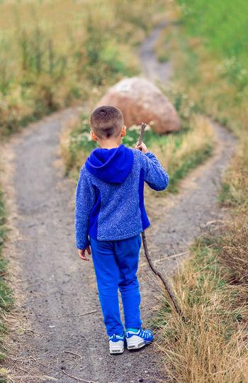 Rear view of boy walking on road