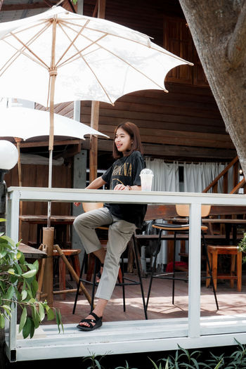 Portrait of woman sitting on chair at cafe