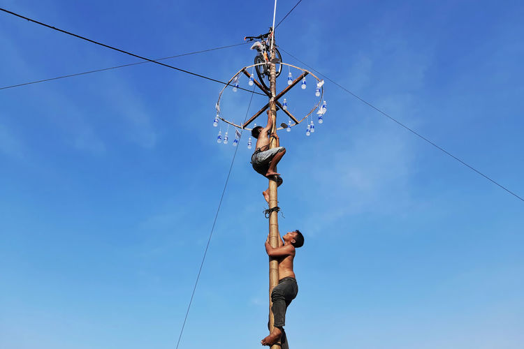 Low angle view of man climbing rope against blue sky