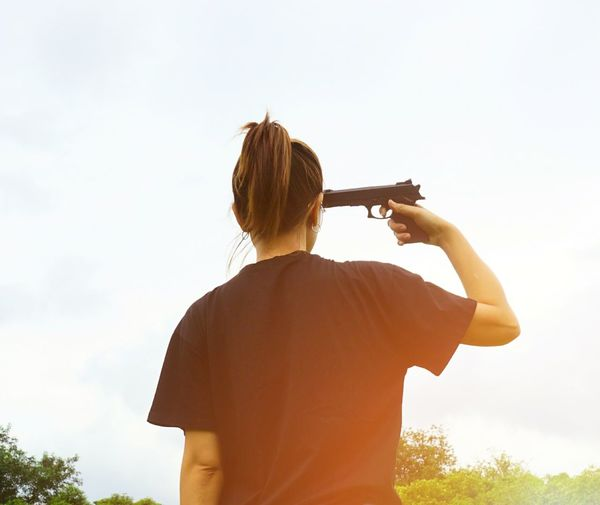 Rear view of woman holding gun to her head
