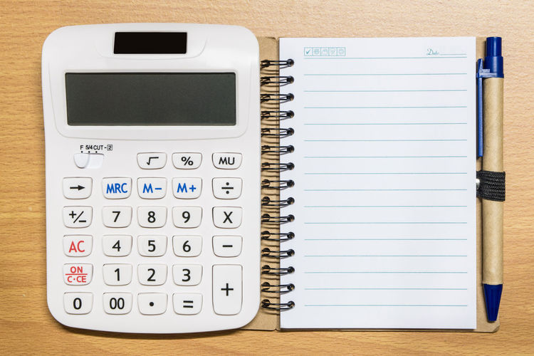High angle view of calculator and paper on table