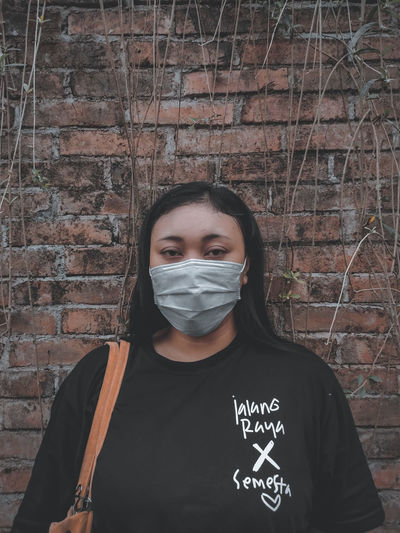 Portrait of young woman wearing mask standing against wall outdoors