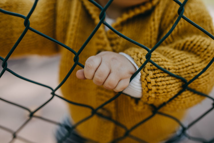 Close-up of toddler hand on chainlink fence