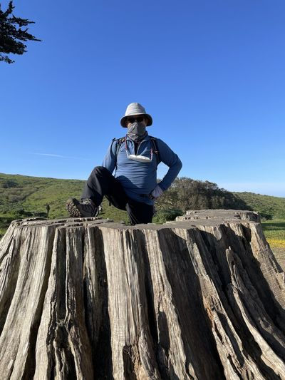 Man sitting on rock against blue sky