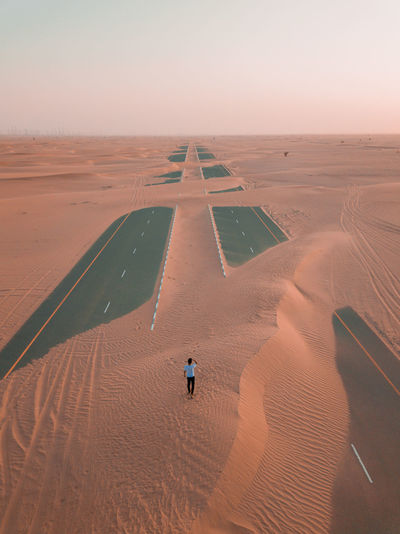 Man Walking On Desert Against Sky