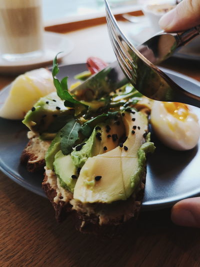avocado bread. Human Hand Egg Yolk Egg Close-up Food And Drink Avocado Guacamole Fried Potato Scrambled Eggs Toasted Fried Egg Prepared Food Brunch Served Toasted Bread Poached Tortilla Chip Nacho Chip Jalapeno Pepper Burrito Spread Tortilla - Flatbread Salsa Mexican Food