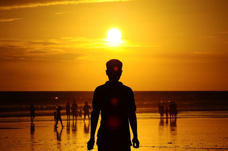 Silhouette man at beach during sunset