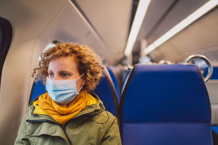 Woman wearing mask sitting in train