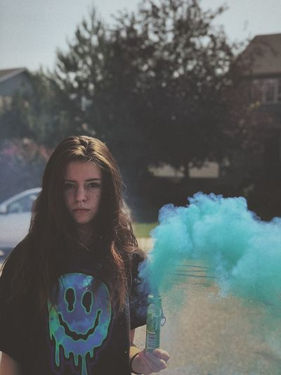 Portrait of young woman holding blue distress flare while standing outdoors