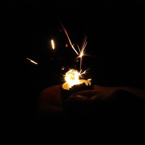 Person holding illuminated burning candles