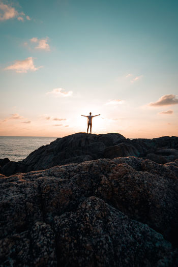 Sky Rock Solid Standing Rock - Object One Person Human Arm Sunset Real People Leisure Activity Arms Outstretched Lifestyles Limb Scenics - Nature Nature Beauty In Nature Rear View Silhouette Full Length Land Arms Raised