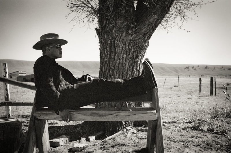 Monochrome Blackandwhite Black And White Black & White Film Film Photography 35mm 35mm Film Man Ranch Rancher Plains Prairie Outdoors Bench Cowboy Cowboy Hat Relaxing Casual Tree Rural Scene Rural Rural America Rurex Countryside Smoke Smoking Smoker Cigarette  Nicotine Tobacco Valley Colorado Giant James Dean Tree Trunk Day Leisure Activity One Person Sitting Land Railing Casual Clothing