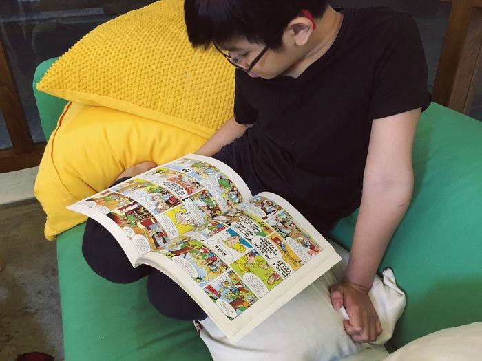 Boy reading comic book Reading A Book Reading Comic Books Boy Black Tshirt Asian  Couch Yellow Pillows Sofa EyeEm Selects One Person Real People Adult Casual Clothing High Angle View Sitting Lifestyles Indoors  Table Leisure Activity Home Interior Furniture Three Quarter Length Relaxation Yellow Arts Culture And Entertainment Seat Clothing