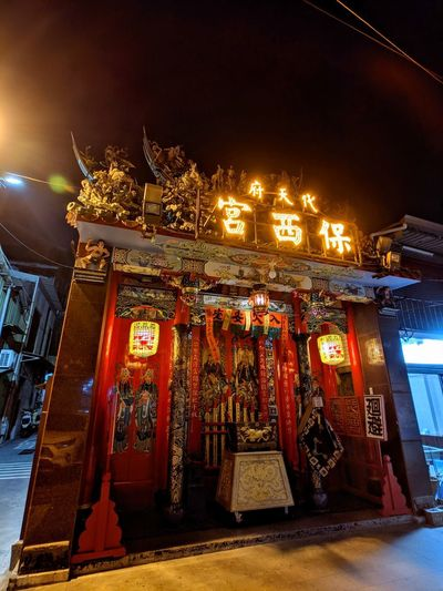Low angle view of illuminated lanterns in city at night
