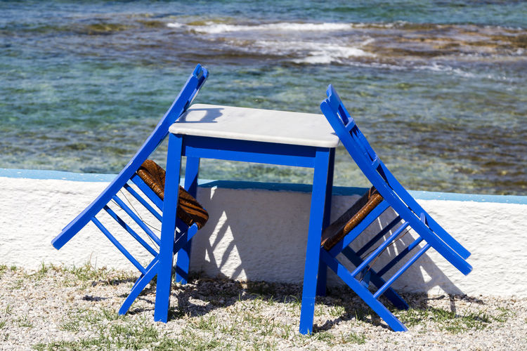 Unused blue painted chairs and table by the sea in the cyclades