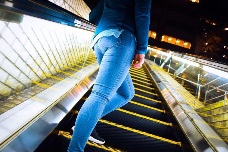 Low Section Of Women Walking On Escalator