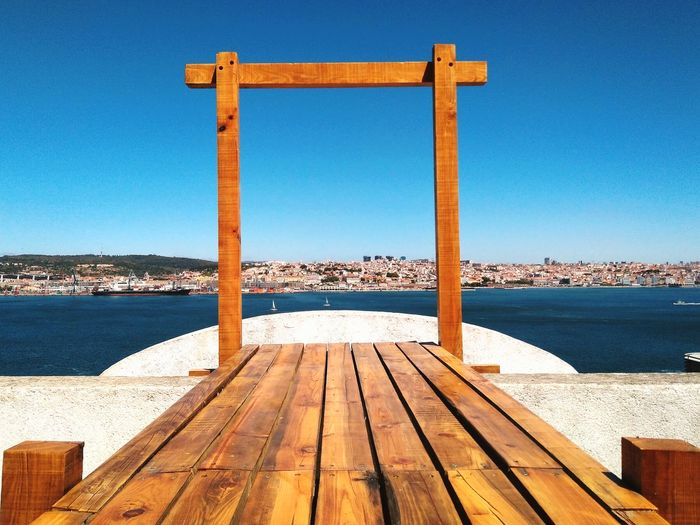 Pier on sea against clear blue sky