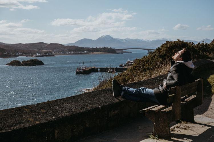 Full length of man sitting on bench against sky